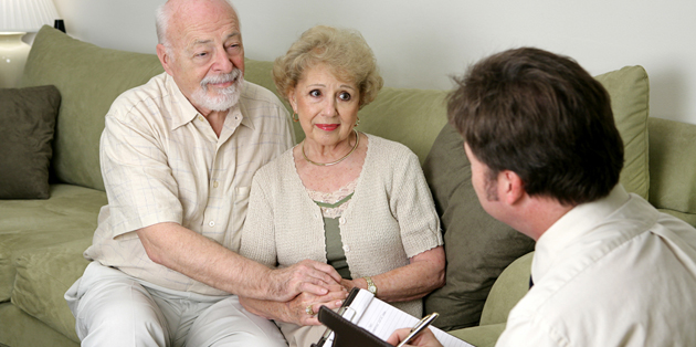 An insurance agent discussing burial  Insurance with two seniors