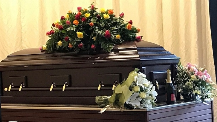 Brown casket with flowers on top during a funeral
