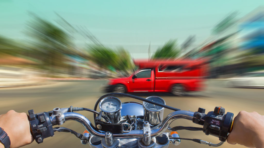 Motorcycle with insurance colliding with a red truck