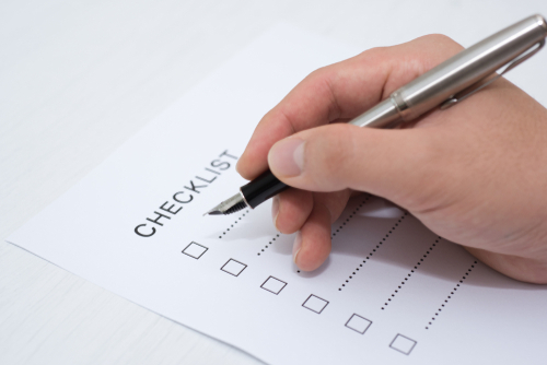 Man making a checklist for what he needs for homeowners insurance