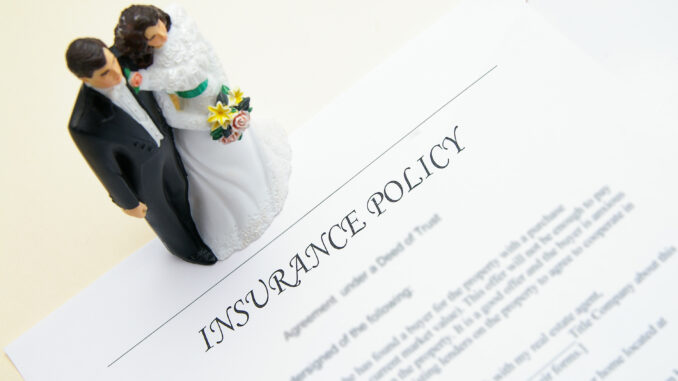 photo of wedding insurance policy with figures of bride and groom